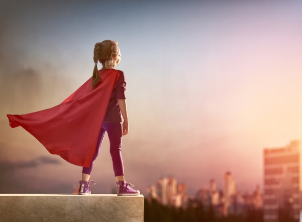 Little girl in red cape plays superhero, standing on rooftop and looking down on city in distance beneath sunset sjy