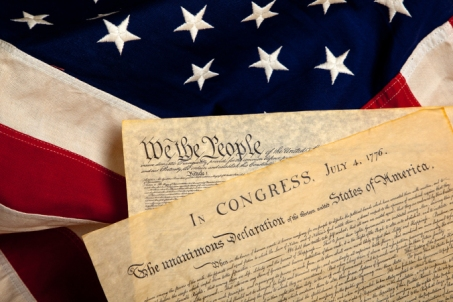 United States' Constitution and Declaration of Independence on a flag background