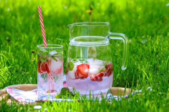 clear pitcher with water and strawberries on tray on grass. Glass beside pitcher has clear water and strawberries plus striped straw