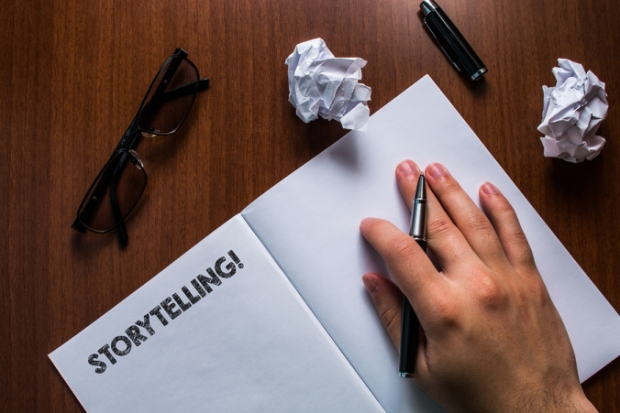 Writing note showing Storytelling. Hand holding pen resting on open notebook, reading glasses lying wooden table.